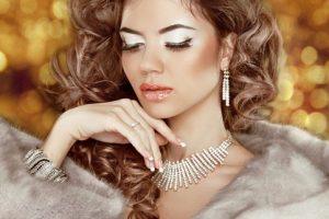Luxury fashion beauty woman in fur coat over golden bokeh backgr